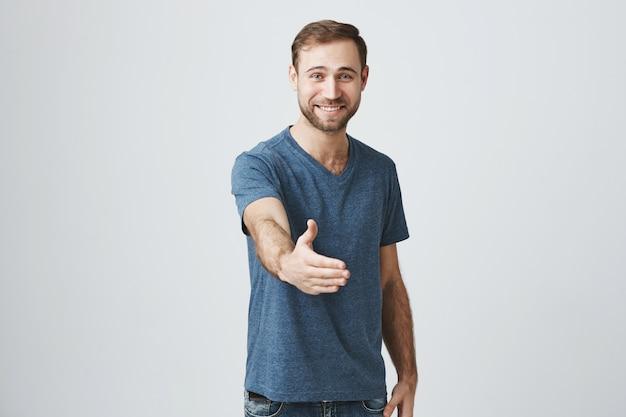 Przyjazny uśmiechnięty mężczyzna wyciągnij rękę do uścisku dłoni, powitanie