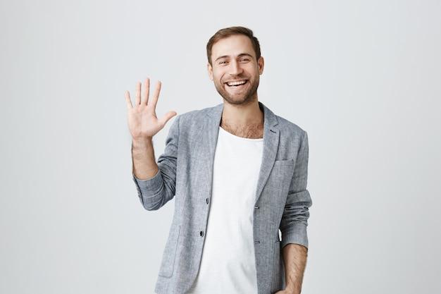 Przyjazny uśmiechnięty przystojny facet macha ręką na powitanie, przywitaj się