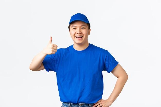 Przyjazny, wesoły azjatycki kurier z kciukiem do góry zadowolony, gratulujący komuś, zatwierdzający lub gwarantujący jakość i bezpieczeństwo przesyłki. facet od dostawy wyglądający na zadowolonego na białym tle