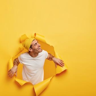 Przyjazny zadowolony mężczyzna odwraca wzrok, stoi w rozdartej papierowej dziurze, ubrany w białą koszulkę