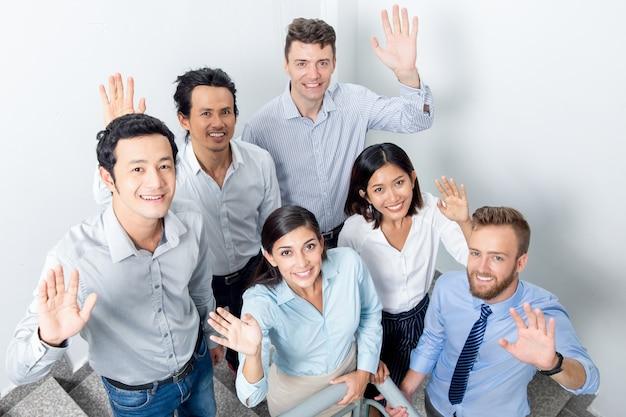 Przyjazny zespół biznesowy machając na schody biurowe
