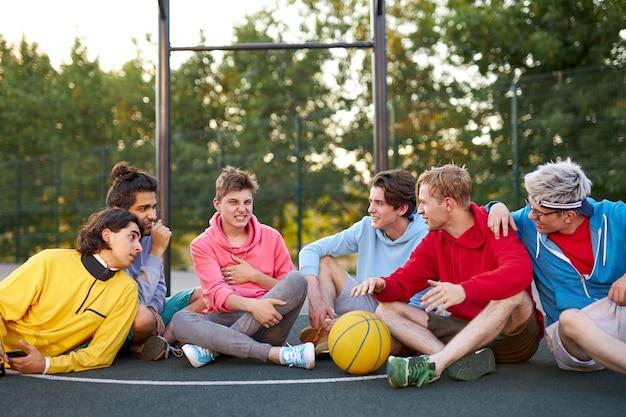 Przyjazny zespół młodych facetów siedzi na boisku do koszykówki