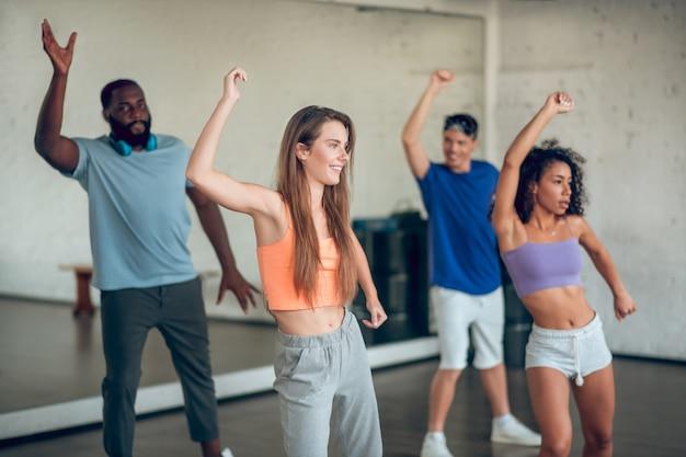 Przyjęcie. grupa młodych ludzi sprawnych w odzieży sportowej robi próby taneczne