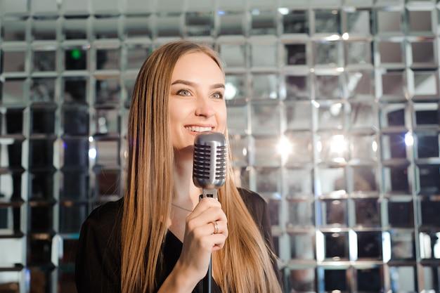 Przyjęcie karaoke. piękna dziewczyna ze śpiewem mikrofonu.