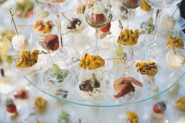 Przyjęcie na weselu. przekąski i kieliszki do wina na szklanym stole.