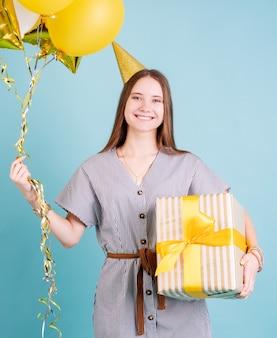 Przyjęcie urodzinowe. młoda kobieta w urodzinowym kapeluszu, trzymając balony i duże pudełko z okazji urodzin na niebieskim tle z miejsca na kopię
