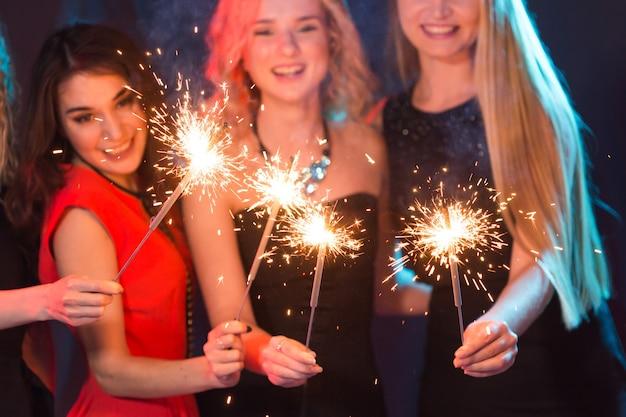 Przyjęcie urodzinowe, nowy rok i święta koncepcja - grupa koleżanek świętujących trzymające ognie z bliska