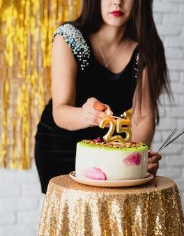 Przyjęcie urodzinowe. piękna brunetka kobieta w czarnej sukience obchodzi urodziny zapalić świeczki 25 na torcie
