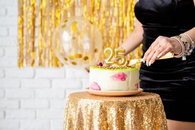 Przyjęcie urodzinowe. piękna brunetka kobieta w czarnej sukience strony trzymając balon z okazji urodzin cięcia ciasta