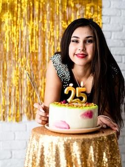 Przyjęcie urodzinowe. piękna kobieta w czarnej sukni obchodzi swoje urodziny, gotowa do dmuchania świeczek na torcie