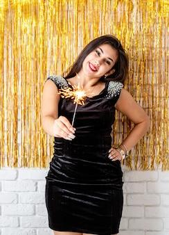 Przyjęcie urodzinowe. piękna młoda kobieta trzymając brylant i balon na złotym tle