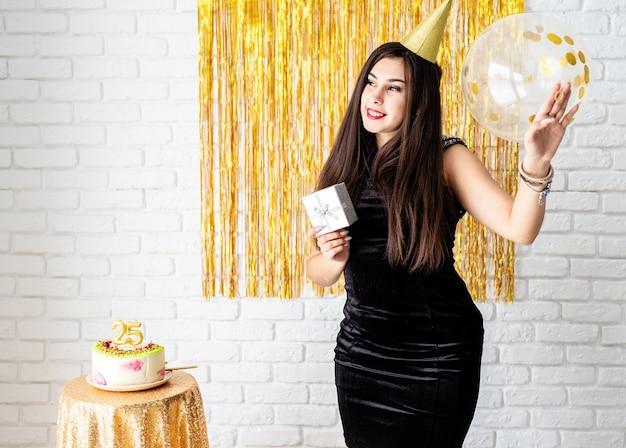 Przyjęcie urodzinowe. piękna młoda kobieta w sukience i urodziny kapelusz trzymając balon na złotym tle