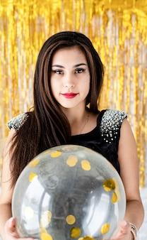 Przyjęcie urodzinowe. piękna uśmiechnięta brunetka kobieta w czarnej sukience obchodzi swoje urodziny trzymając balon