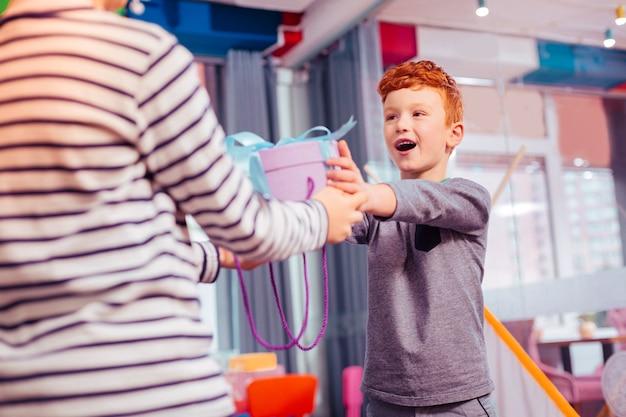 Przyjęcie urodzinowe. przystojny rudowłosy chłopak wyrażający pozytywne nastawienie podczas dawania prezentu