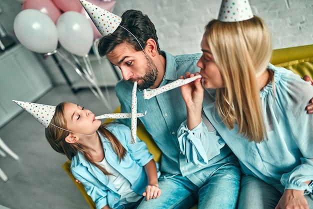 Przyjęcie urodzinowe. rodzina obchodzi urodziny córki, bawi się na imprezie, nosi czapki urodzinowe. rodzinne cudowne chwile.