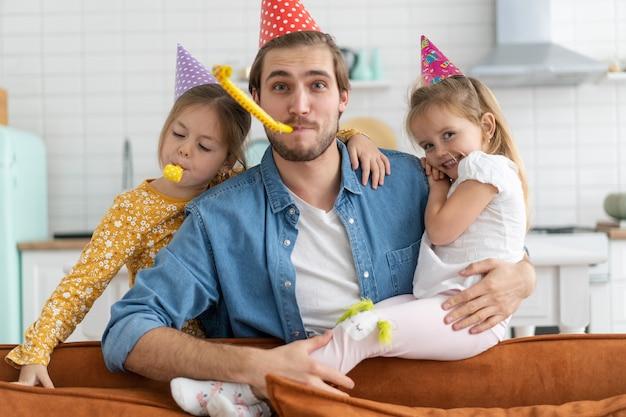 Przyjęcie urodzinowe. rodzina obchodzi urodziny córki, bawi się na imprezie, nosi czapki urodzinowe.