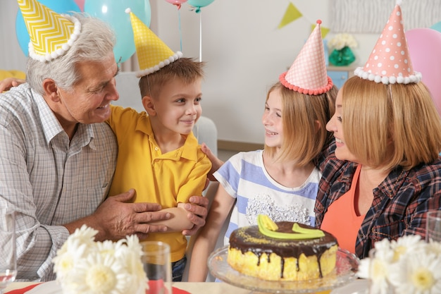 Przyjęcie urodzinowe. rodzina siedzi przy serwowanym stole