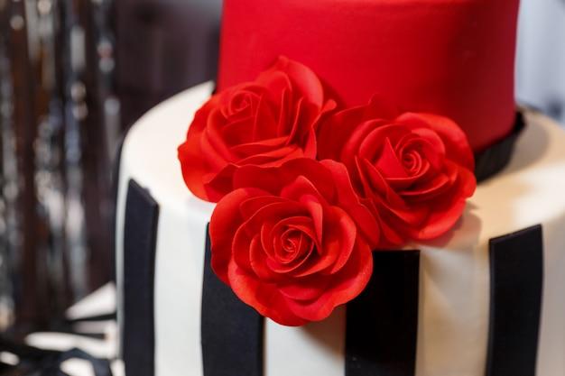 Przyjęcie urodzinowe z pięknym dużym ciastem, ozdobione różami i stojące na beczce. smaczne słodycze o kremowym wystroju w kolorach czarnym, czerwonym, białym