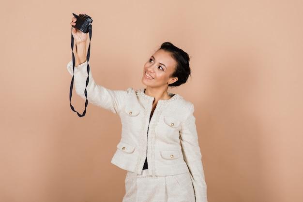 Przyjemna afrykańska młoda kobieta trzyma aparat