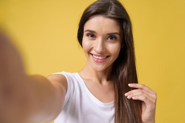 Przyjemna atrakcyjna dziewczyna co selfie w studio i śmiejąc się. przystojna młoda kobieta z brązowymi włosami robi sobie zdjęcie na jasnożółtym tle.