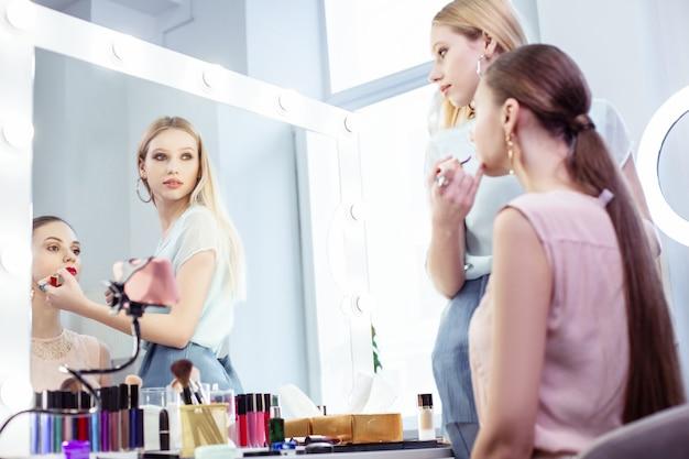 Przyjemna blond wizażystka patrząca w lustro stojąc ze swoim klientem