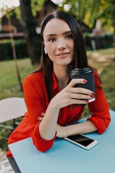 Przyjemna brunetka w czerwonej koszuli miło spędza czas w ulicznej kawiarni.