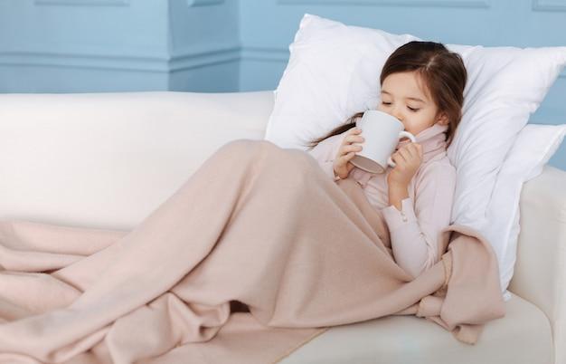 Przyjemna, chora dziewczynka cierpiąca na grypę i pijąca herbatę leżąc w swoim łóżku