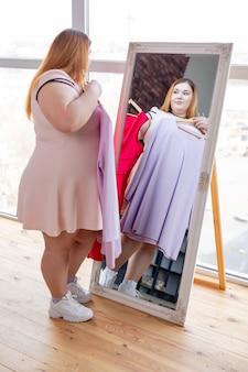 Przyjemna, dobrze wyglądająca kobieta stojąca przed lustrem podczas wybierania sukienek