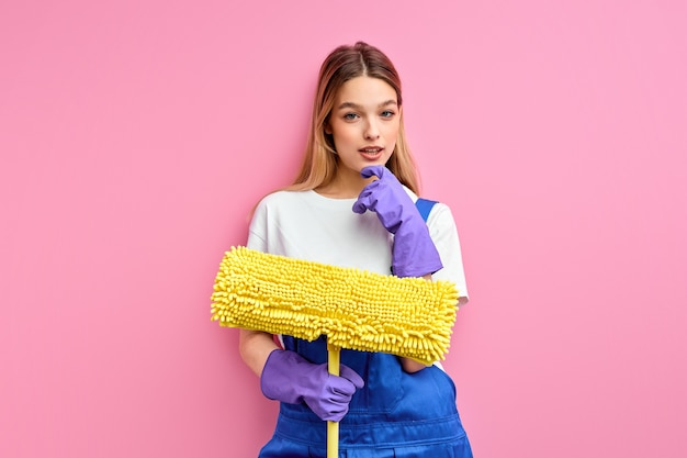 Przyjemna domowa żona w dobrym humorze trzymająca sprzęt do sprzątania, szmata do podłogi, ubrana w niebieski kombinezon