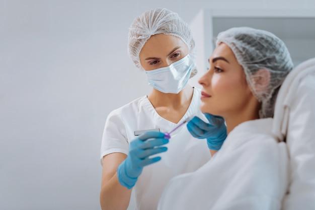 Przyjemna, inteligentna kobieta wykonująca zabiegi kosmetyczne pracując jako kosmetyczka