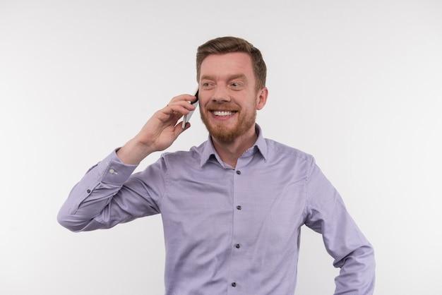Przyjemna interakcja. radosny szczęśliwy człowiek uśmiecha się podczas rozmowy przez telefon
