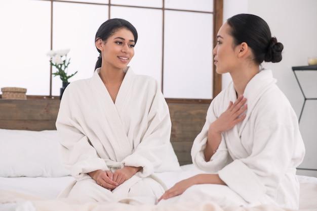 Przyjemna interakcja. wesoła miła zachwycona kobieta patrząc na swojego przyjaciela, wskazując na siebie