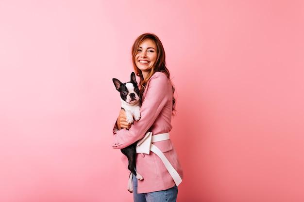 Przyjemna kaukaska kobieta w różowym stroju obejmującym szczeniaka. wspaniała biała dziewczyna trzyma buldoga francuskiego z uśmiechem.