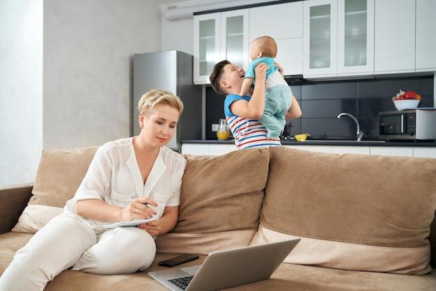 Przyjemna kobieta pracuje na laptopie, podczas gdy synowie bawią się razem