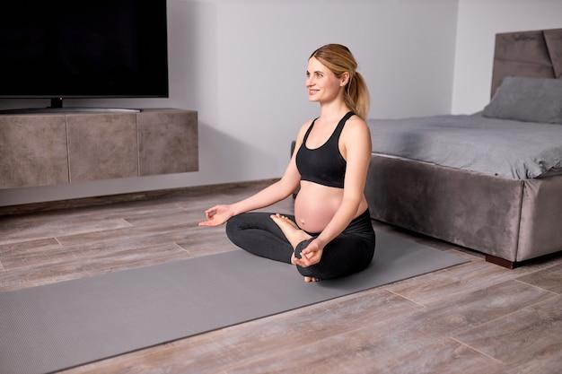 Przyjemna kobieta w ciąży medytuje na podłodze w domu ze skrzyżowanymi nogami