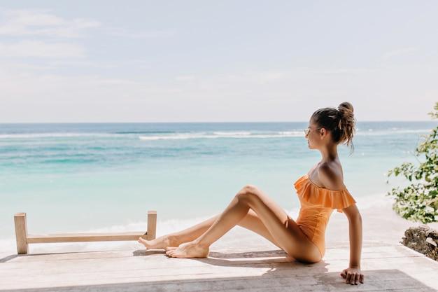 Przyjemna kobieta w romantycznym stroju kąpielowym siedzi na ziemi i patrzy na horyzont. zewnątrz zdjęcie szczupłej białej modelki chłodzenie na wybrzeżu morza pod bezchmurnym niebem.