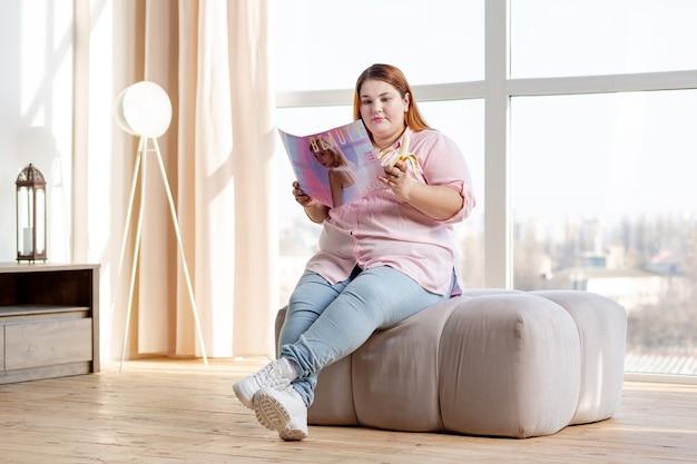 Przyjemna kobieta z nadwagą czytająca gazetę w domu podczas jedzenia banana