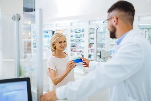 Przyjemna komunikacja. całkiem dojrzała kobieta, która ma uśmiech na twarzy podczas przyjmowania paczki z tabletkami