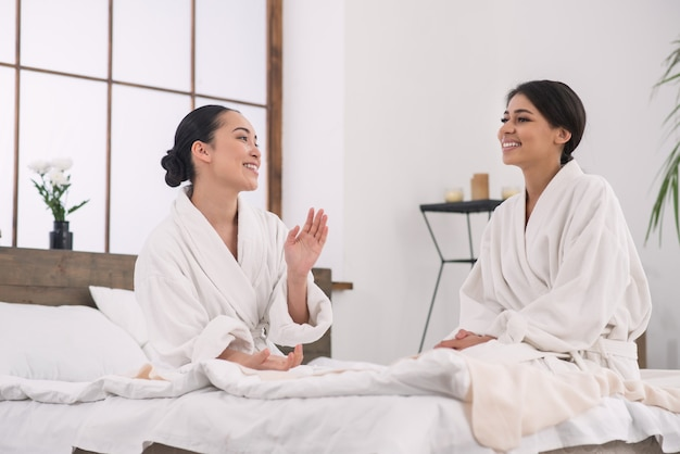 Przyjemna komunikacja. pozytywnie zachwyceni przyjaciele rozmawiający ze sobą podczas pobytu w salonie spa