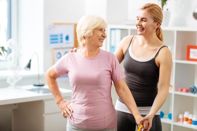 Przyjemna komunikacja. przystojna starsza kobieta uśmiecha się podczas rozmowy z trenerem