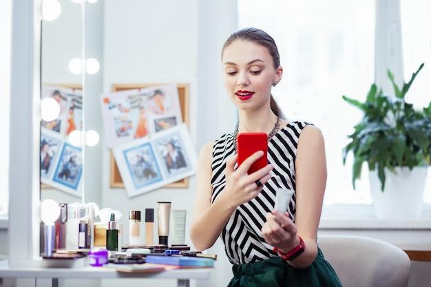 Przyjemna ładna kobieta uśmiecha się podczas robienia zdjęcia kremu