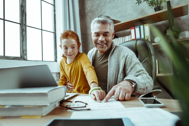 Przyjemna lekcja. zachwycona pozytywna dziewczyna uśmiecha się podczas nauki z ojcem