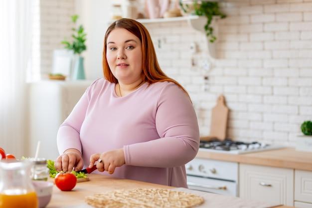 Przyjemna miła kobieta przygotowująca zdrową sałatkę będąc na diecie