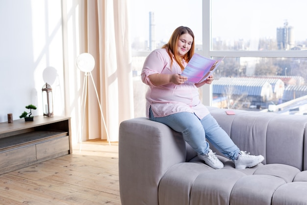 Przyjemna miła kobieta siedzi na kanapie i czyta magazyn kosmetyczny
