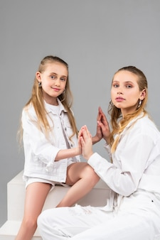 Przyjemna młoda dziewczyna w białych szortach i kurtce, trzymająca dłonie na dłoniach swojej podobnej siostry