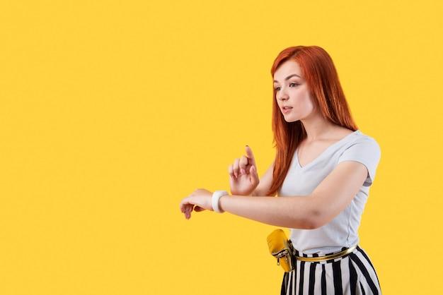 Przyjemna młoda kobieta nosząca smartwatch na nadgarstku, która używa smartwatcha