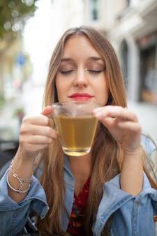 Przyjemna młoda kobieta pachnąca pachnącą zieloną herbatą