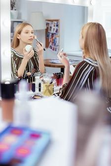 Przyjemna młoda kobieta patrząca na siebie w lustrze podczas nakładania makijażu