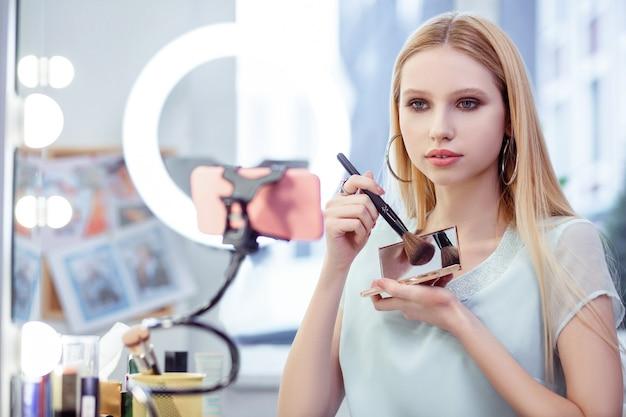 Przyjemna młoda kobieta pokazująca swoje kosmetyki w aparacie, polecając je swoim widzom