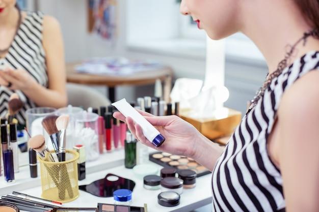 Przyjemna młoda kobieta siedząca przed lustrem podczas używania kosmetyków do twarzy